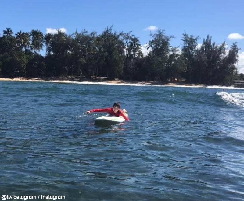 休暇中、ハワイでサーフィンをするミナ